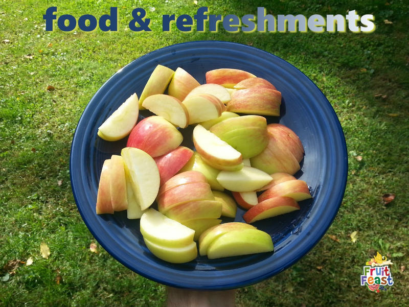 Food & Refreshments - sliced apple on blue plate held in hand above green grass