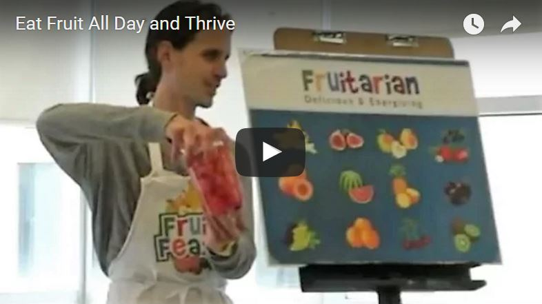 Video still - man giving presentation. Same man holding container of cut watermelon, and he stands beside poster stating fruitarian with fruit images on poster
