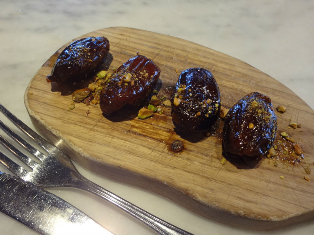 Roasted medjool dates on small wooden serving board with minced pistachios