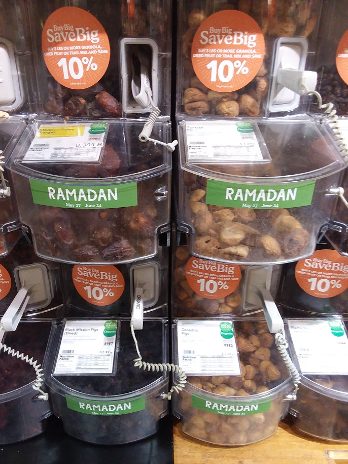 Dates and figs in bulk food containers with Ramadan signs