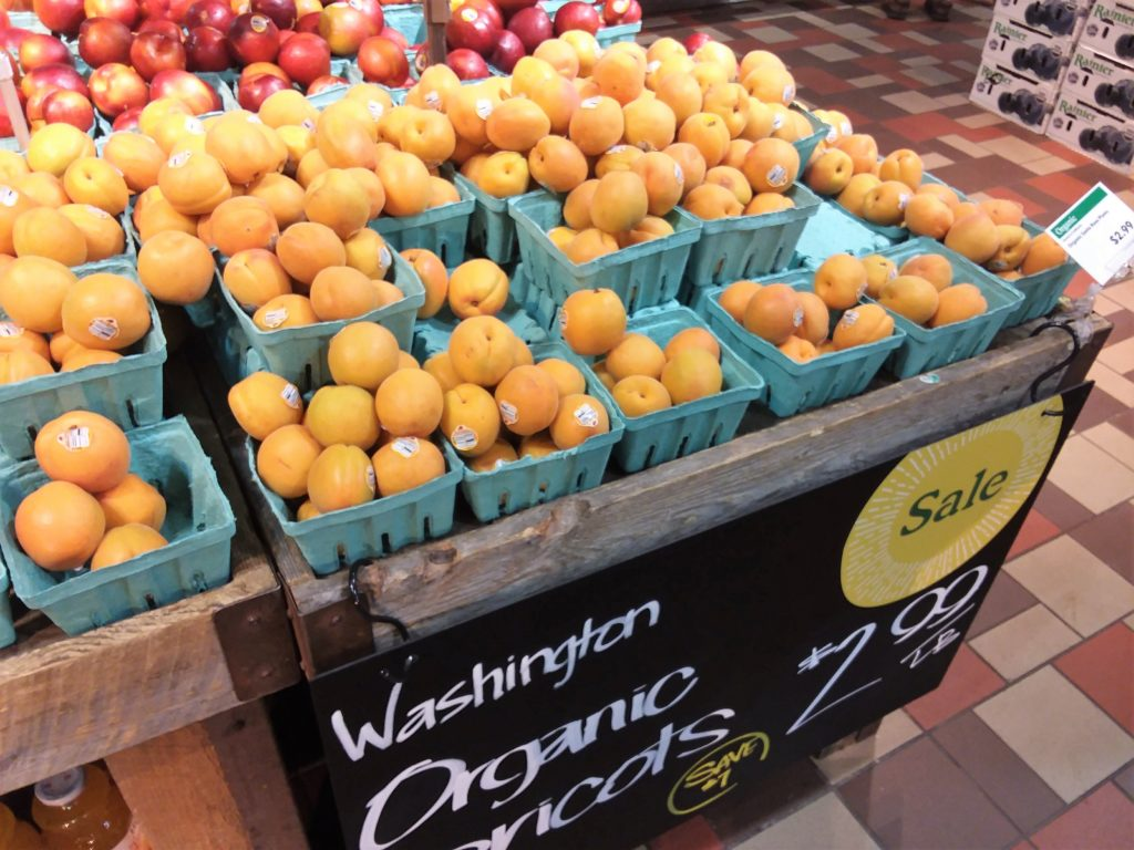 Apricots displayed at grocery store with large sale sign 2.99 per pound