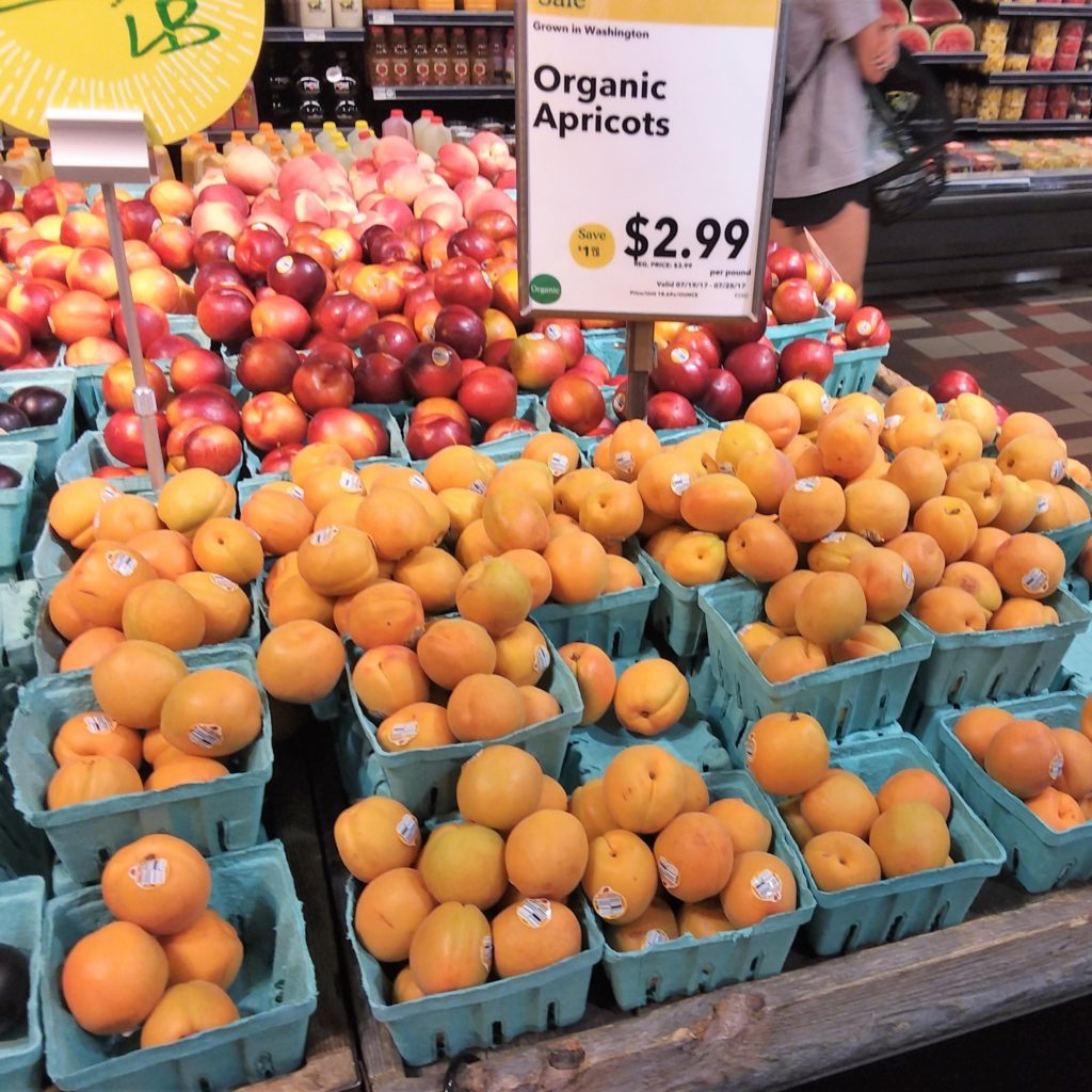 Apricots displayed at grocery store with sale sign $2.99 per pound