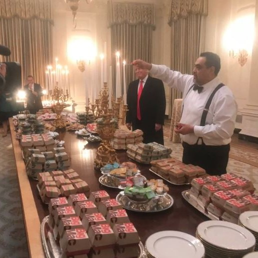 Buffet of fast food burgers in a White House room with Donald Trump and staffer standing by table