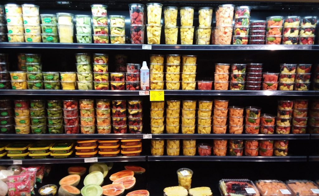 Cut-fruit display at Whole Foods Market. Containers with kiwis, pineapple, berries, papaya, cantaloupe and more
