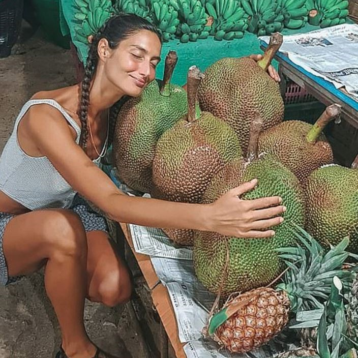 Woman Kneeling Beside Display Of Jackfruit At Market